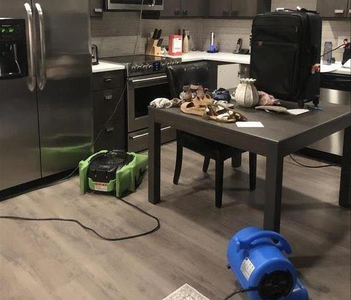kitchen with stainless steel appliances and one green and blue air movers on the floor.