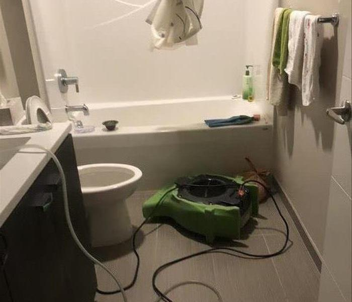 Bathroom with a green air mover in front of the bathtub.
