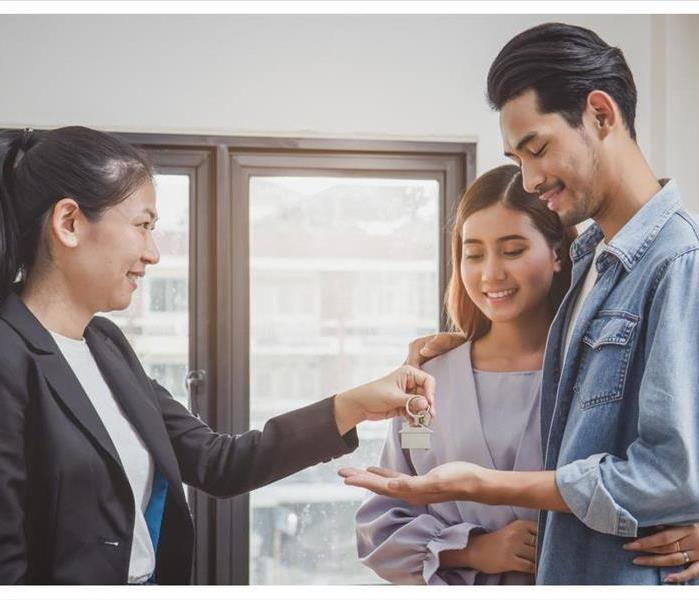 Happy asian couple receiving apartment key from real estate agent
